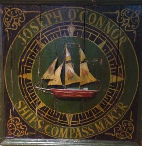 wooden board graphic of ship with lettering ships compass